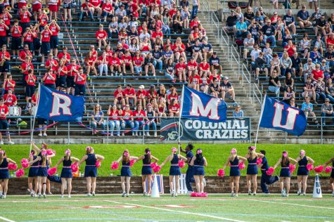 The Colonials cheerleaders carry the RMU letters out onto the field before the start of the team's first home game of 2018. September, 17, 2018 (David Auth/RMU Sentry Media)