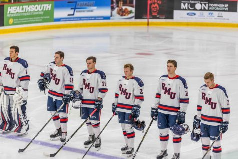 The Robert Morris Men's hockey team stands in unison at the blue line during the playing of the National Anthem at Colonials Arena.