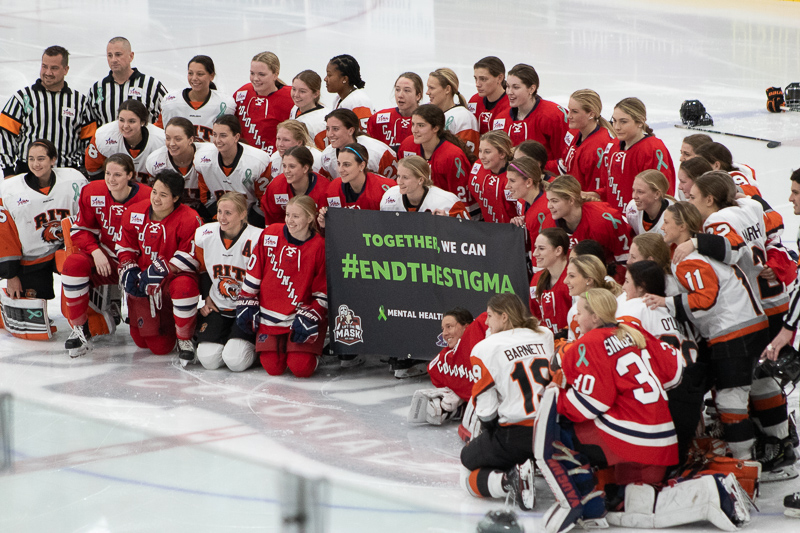Both teams gather around the #EndtheStigma banner before the start of the Mental Health Awareness game. Neville Island, PA Friday Jan. 25, 2019. (RMU Sentry Media/Samuel Anthony)