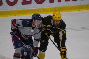 RMU's Aidan Spellacy and AIC's Tobias Fladeby line up for a faceoff on January 25, 2020 Photo credit: Garret Roberts