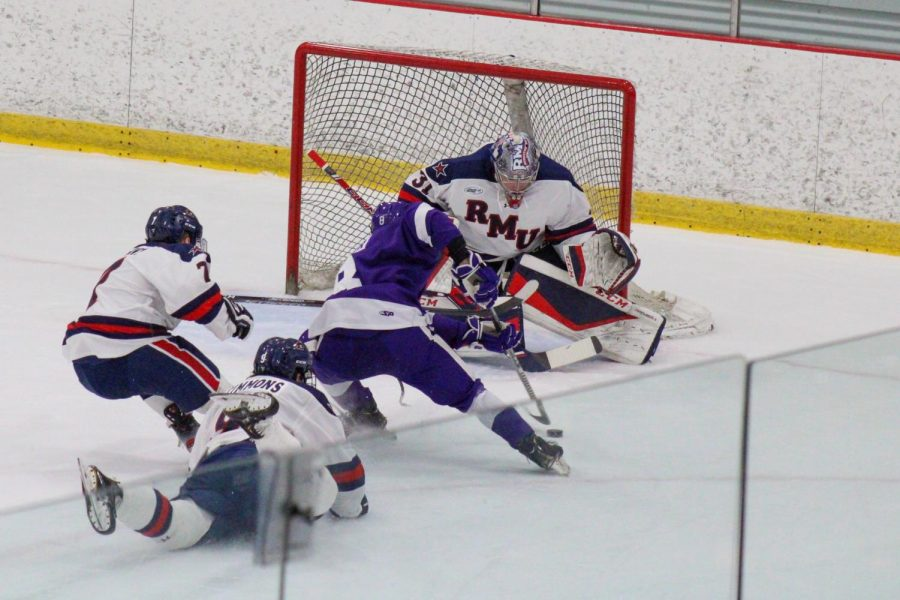 Walker Sommer attempts a shot against Noah West in the Purple Eagles' 3-2 double-overtime win against RMU. Photo Credit: Nathan Breisinger