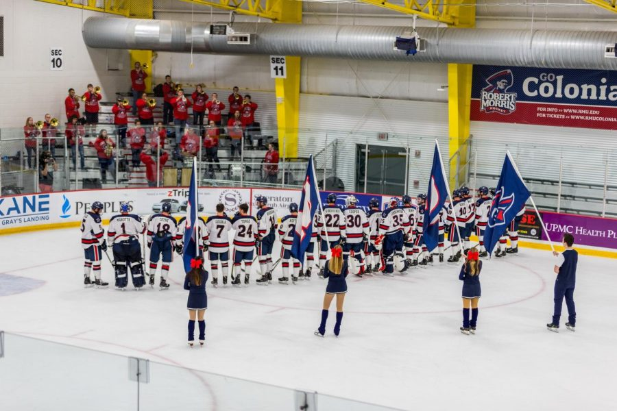 The hockey team listens to the RMU band play the alma mater after their game.