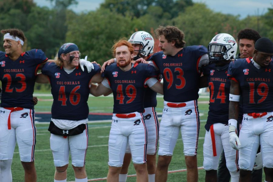 RMU football links arms after their win over Howard.